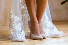 Plciowe nogi panna młoda Panna młoda stoi na drewnianej podłoga, but w śmietanka butach, i pokazuje jej piękne nogi Zdjęcie Royalty Free