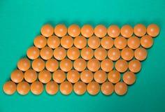 Píldoras anaranjadas en verde Imagen de archivo