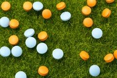 Píldoras anaranjadas y azules que se derraman en la hierba verde Fotos de archivo libres de regalías