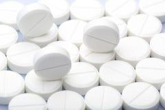 Píldoras blancas en un fondo blanco Fotos de archivo libres de regalías