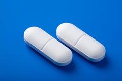 Píldoras blancas sobre azul Foto de archivo libre de regalías