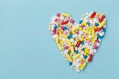 Píldoras coloridas de la droga en la forma del corazón en el fondo azul, concepto farmacéutico Imagen de archivo