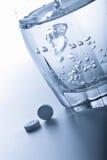 Píldoras de la aspirina y vidrio de agua Fotos de archivo libres de regalías