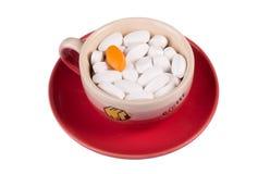 Píldoras en una taza de café Foto de archivo
