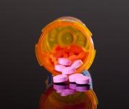 Píldoras púrpuras de la botella anaranjada de la droga Imagen de archivo libre de regalías