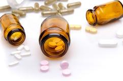 Píldoras que se derraman fuera de la botella de píldora Fotografía de archivo