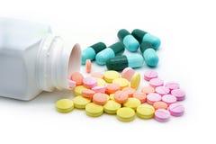 Píldoras que se derraman fuera de la botella de píldora Foto de archivo libre de regalías