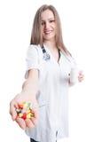 Píldoras que se sostienen y de ofrecimientos del doctor joven y amistoso de la mujer Fotos de archivo