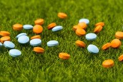 Píldoras redondas anaranjadas y azules dispersadas en la hierba verde Fotografía de archivo libre de regalías