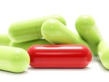 Píldoras rojas y verdes en blanco Foto de archivo libre de regalías
