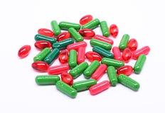 Píldoras rojas y verdes en el fondo blanco Fotografía de archivo