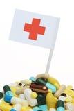 Píldoras y bandera de la Cruz Roja Imagen de archivo libre de regalías