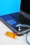 Píldoras y ordenador portátil del estetoscopio Fotografía de archivo