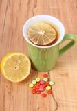 Píldoras y té caliente con el limón para los fríos, el tratamiento de la gripe y que moquea Imágenes de archivo libres de regalías