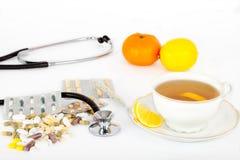 Píldoras y té caliente para los fríos y la gripe Foto de archivo libre de regalías