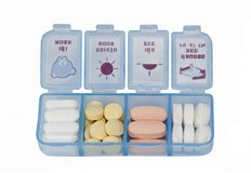 Píldoras y vitaminas en una caja azul de la píldora Imágenes de archivo libres de regalías