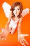 Pleading Angel. Redheaded girl with white outfit and wings. Arms reaching, looking upward. Taken in studio with an orange background from a high viewpoint royalty free stock photos