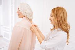 Pleasan妇女helpng她的穿礼服的母亲 免版税库存照片
