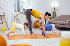 Pleasant active children training together with their mother. Sports activities. Pleasant active children repeating he movements while working out together with stock images