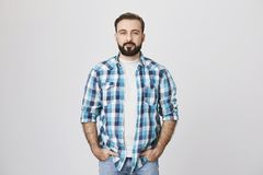Pleasant adult bearded man with hands in pockets wearing blue checked shirt while standing over gray background. Guy. Enters elevator and waits until he arrive Royalty Free Stock Photos