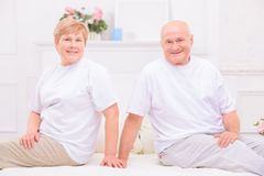 Pleasant adult couple lying on bed Stock Images