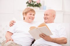 Pleasant adult couple lying on bed Stock Photo