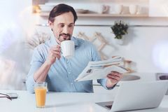 Pleasant adult man reading newspaper in the morning Stock Photography