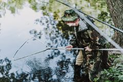 Aged professional concentrated angler using fishing equipment. Pleasant aged man holding nets while fishing in the river on the weekend stock photos
