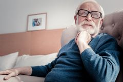 Pleasant aged man sitting at home. Thoughtful mood. Pleasant good looking aged men sitting at home and holding his chin while thinking about his life Stock Photo