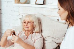 Pleasant aged woman holdign bottle with pills. stock images