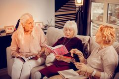 Pleasant aged women sitting together on the sofa royalty free stock image