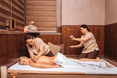 Pleasant Asian women doing oil massage for the client. At work. Pleasant Asian women doing oil massage for the client while working in the spa center royalty free stock photos