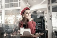 Kind mature woman being deep in her thoughts. Pleasant atmosphere. Pretty elegant female expressing positivity while waiting for her partner stock photography