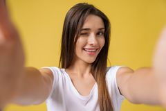 Pleasant attractive girl making selfie in studio and laughing. Good-looking young woman with brown hair taking picture. Of herself on bright yellow background stock image