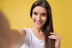 Pleasant attractive girl making selfie in studio and laughing. Good-looking young woman with brown hair taking picture. Of herself on bright yellow background stock photography