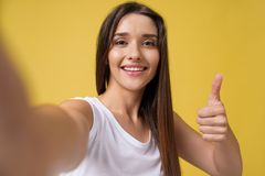 Pleasant attractive girl making selfie in studio and laughing. Good-looking young woman with brown hair taking picture. Of herself on bright yellow background royalty free stock photography