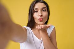 Pleasant attractive girl making selfie in studio and laughing. Good-looking young woman with brown hair taking picture. Of herself on bright yellow background royalty free stock photo