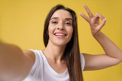 Pleasant attractive girl making selfie in studio and laughing. Good-looking young woman with brown hair taking picture. Of herself on bright yellow background royalty free stock images