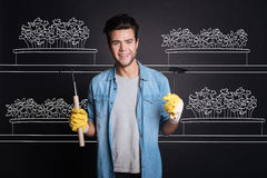 Pleasant attractive man holding gardening tools. Stock Photography