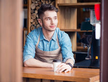 Pleasant barista drinking coffee Stock Images