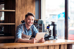 Pleasant barista standing at the counter. Ready to work for my guests. Pleasant smiling delighted handsome barista standing at the counter and expressing royalty free stock images