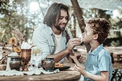 Pleasant bearded father washing his sons face