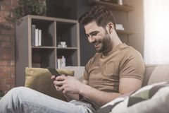 Pleasant bearded guy is surfing internet using smartphone royalty free stock photo