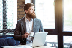 Pleasant bearded man drinking coffee Royalty Free Stock Photography