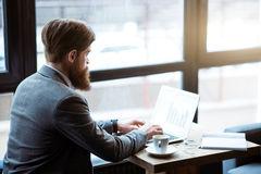Pleasant bearded man sitting at the table Royalty Free Stock Photography