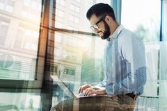 Pleasant bearded man working with the laptop and smiling. Best employer. Pleasant bearded bespectacled man in the office keeping the laptop on his knees working Royalty Free Stock Photos