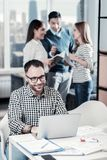 Pleasant bespectacled man sitting and working with the laptop. Work and me. Pleasant bespectacled unshaken men sitting in the office by the table working with Stock Photo