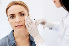 Pleasant blonde woman having a botox injection stock photo