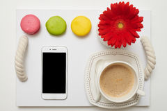Pleasant breakfast with coffee, macaroons and mobile phone on t. Flat lay picture of romantic breakfast with coffee, macaroons and mobile phone on service tray Stock Photo
