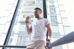 Pleasant bristled guy is enjoying espresso. City lifestyle. Low angle of satisfied bearded man in casual clothes is standing on staircase with coffee. He is Royalty Free Stock Photography